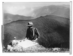 Historic image of forest ranger with map on a mountain overlooking a forested landscape.