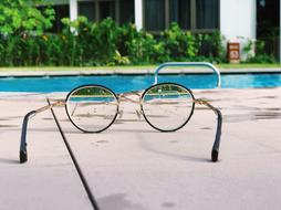 Spectacles lying on the side of a swimming pool.